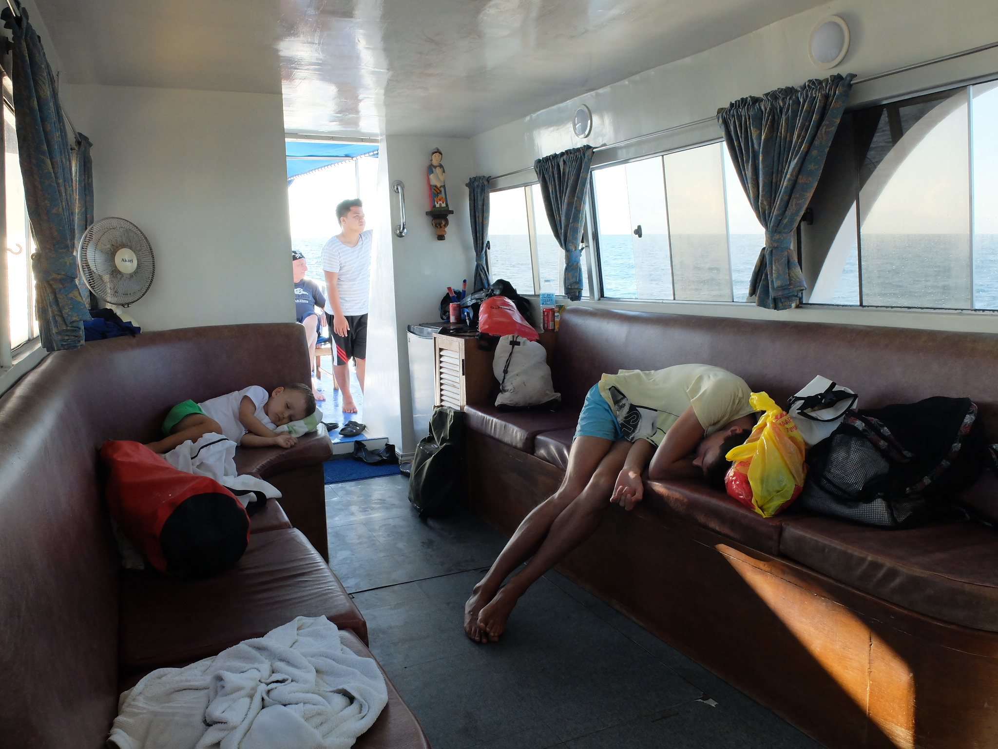 Zmęczone chłopaki śpią pod podkładem podczas powrotu na Siquijor
